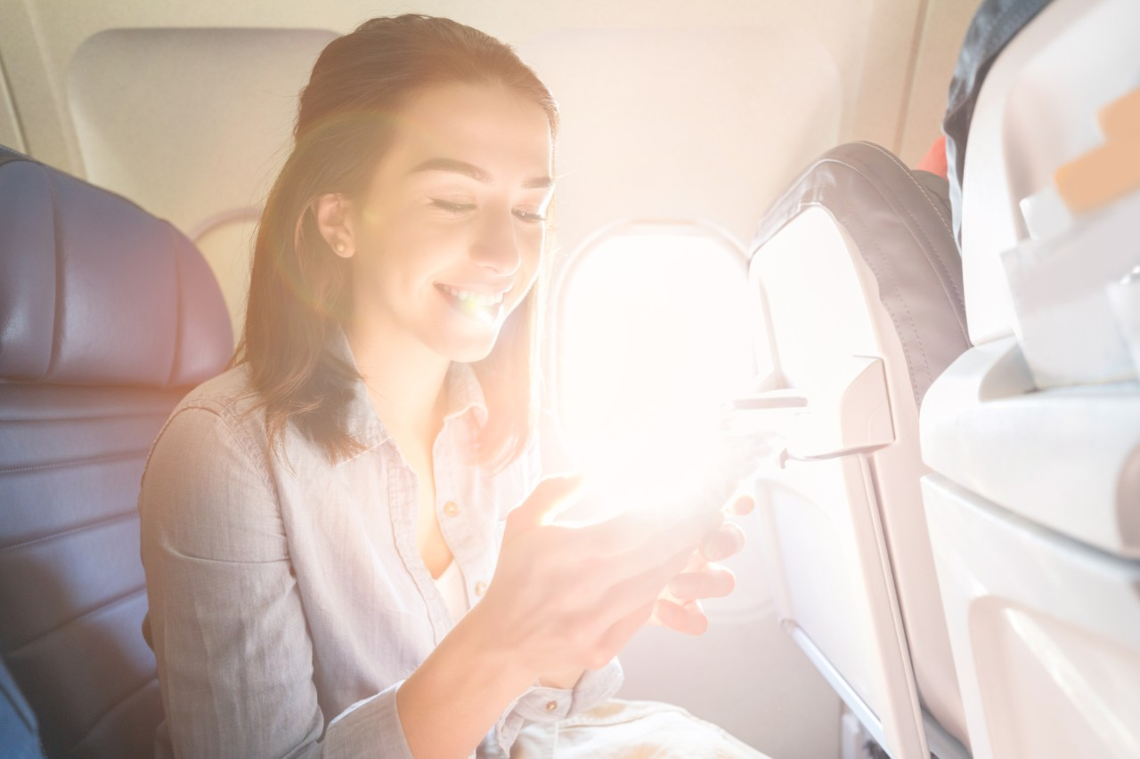 Cheerful young woman uses smart phone while on a commercial flight. The sun is streaming through the window next to her.