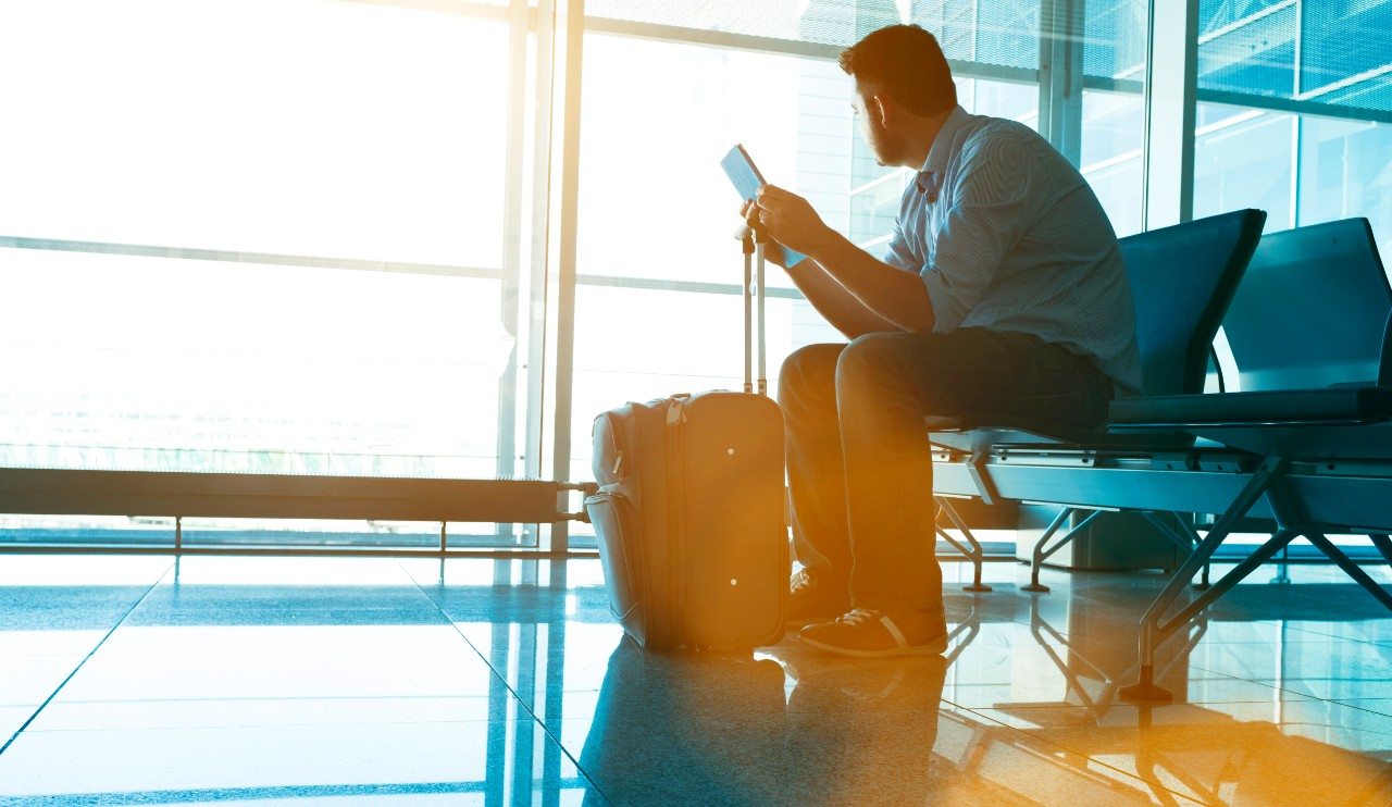 Traveller sits in at chair at an airport terminal waiting for a plane. He holds a digital tablet and looks out through the windows towards the planes. The sun shines. A suitcase stands infront of the man.