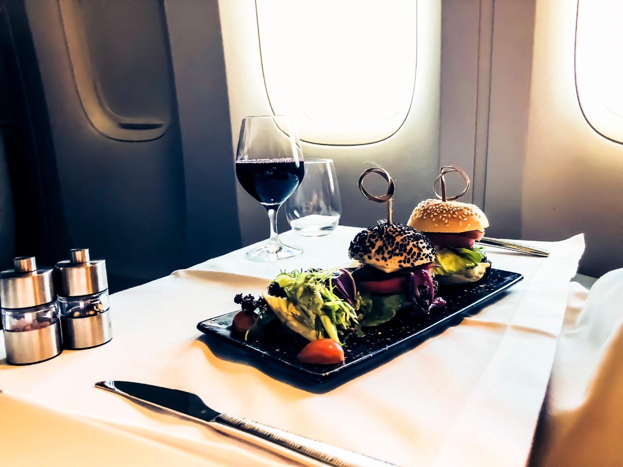 Luxury food served on an aircraft with a glass of wine and metal cutlery
