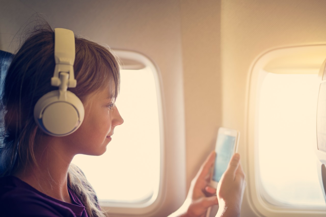 Teenage girl sitting on a plane and using her mobile smartphone