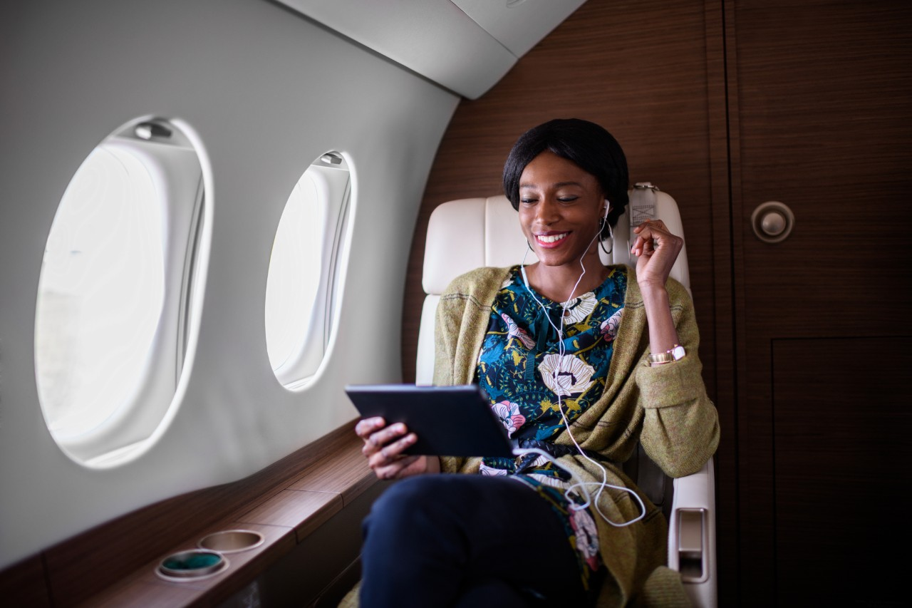 Woman sitting inside private jet airplane and holding tablet device