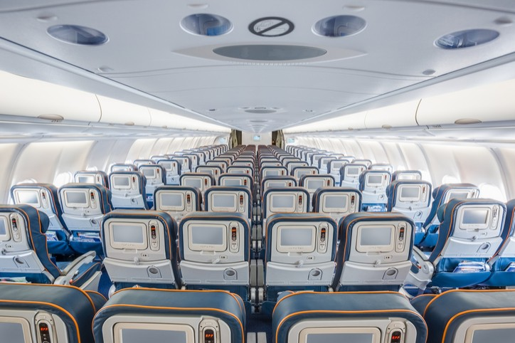 View from back of airplane interior with blue seats and orange headrests