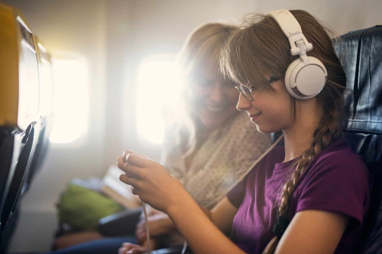 Mother and daughter travelling by plane. They are sitting comfortably and smiling happily. Daughter is using the smartphone and mother is also looking at her phone.