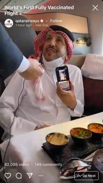 Qatari man seated on the Qatar Airways flight holding a mobile phone