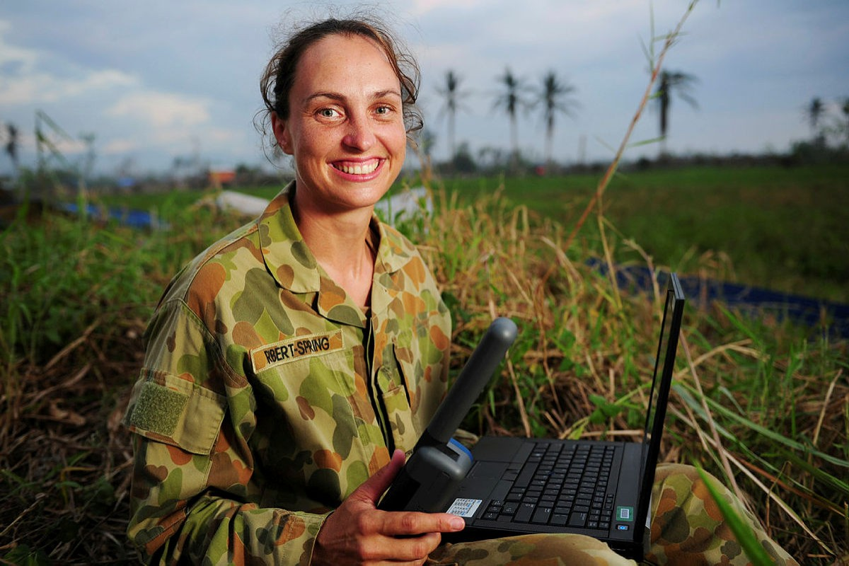 Female Australian Army Signaller sitting outside with a laptop and holding an Inmarsat IsatPhone handheld satellite phone